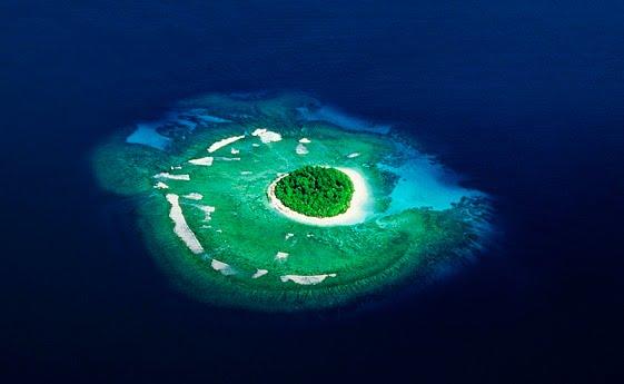 Тонга, острова архипелага Вавау, вид с высоты на маленький необитаемый островок, окруженный пляжем и мелководьем, лагуна, окруженная рифом.